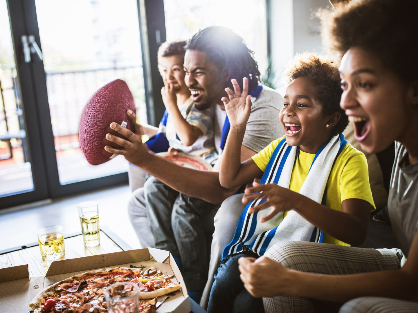 Fans cheering for their football team and eating pizza