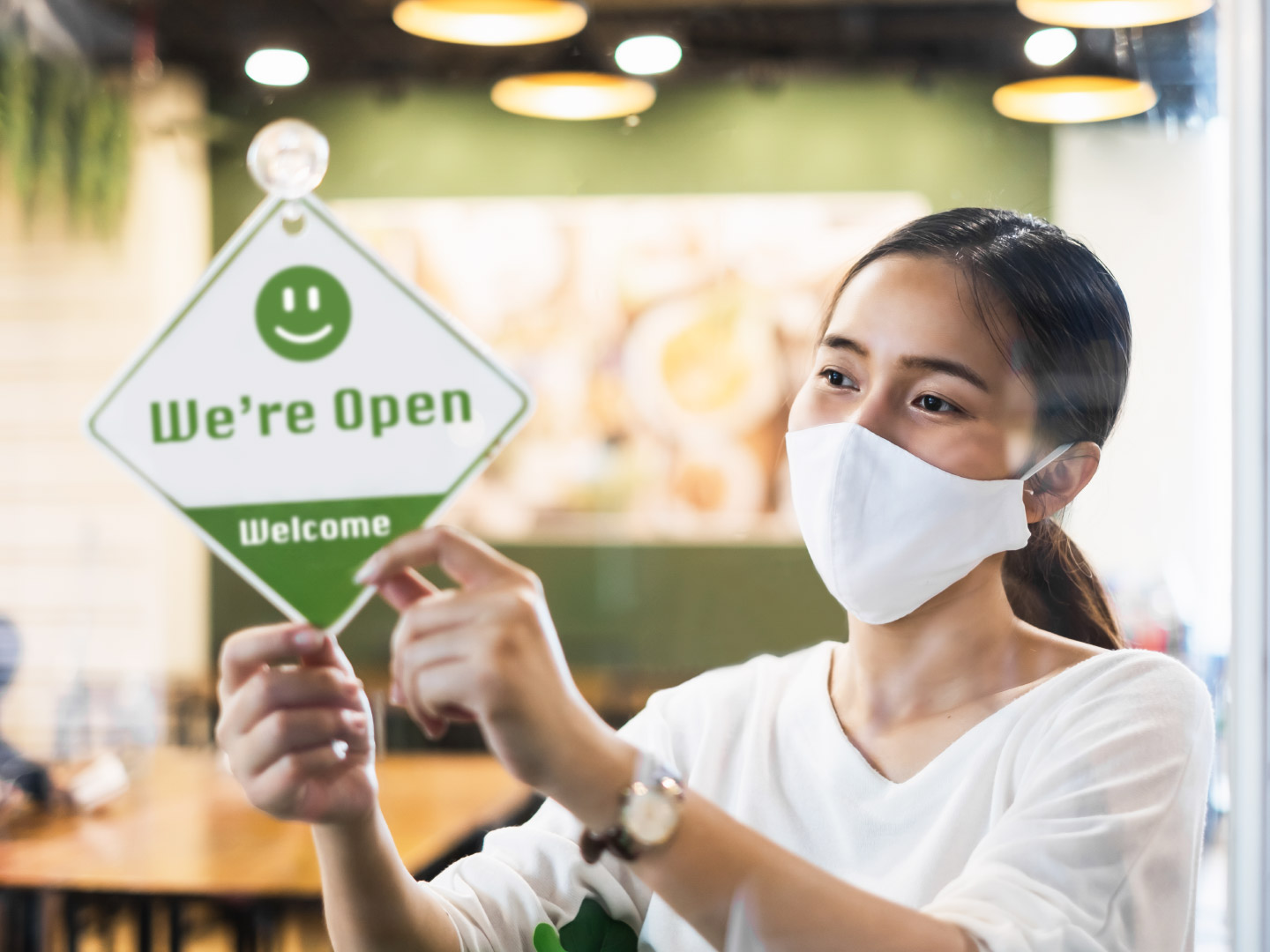 A young Asian-American woman wearing a mask flips the sing on her store to display that it is open