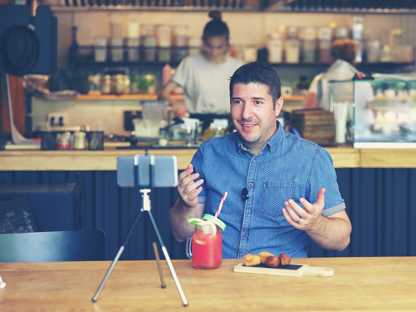 Caucasian man video blogging his reviews of a restaurants newest drink and menu item