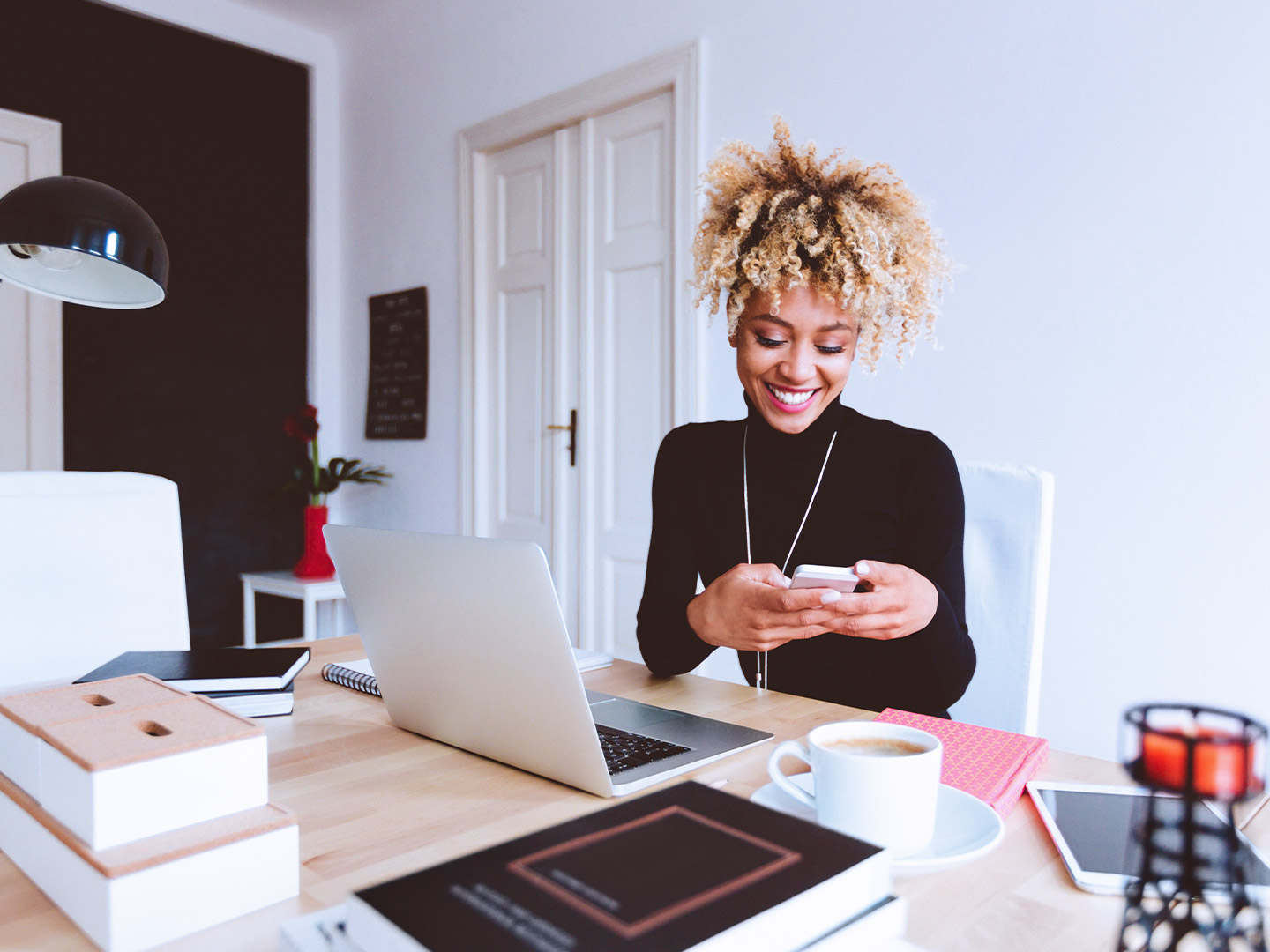 African American woman scrolling through social media while in her work from home office
