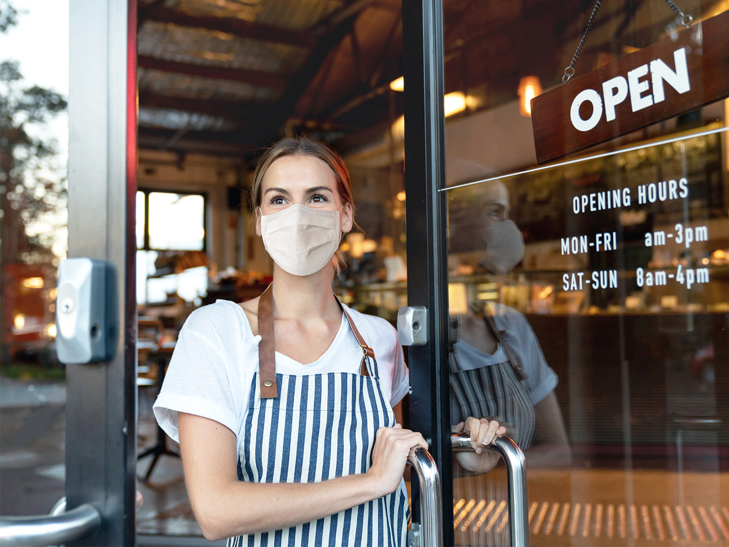 Caucasian woman wearing a mask and holding the door of her store open ready to welcome visitors back once again.