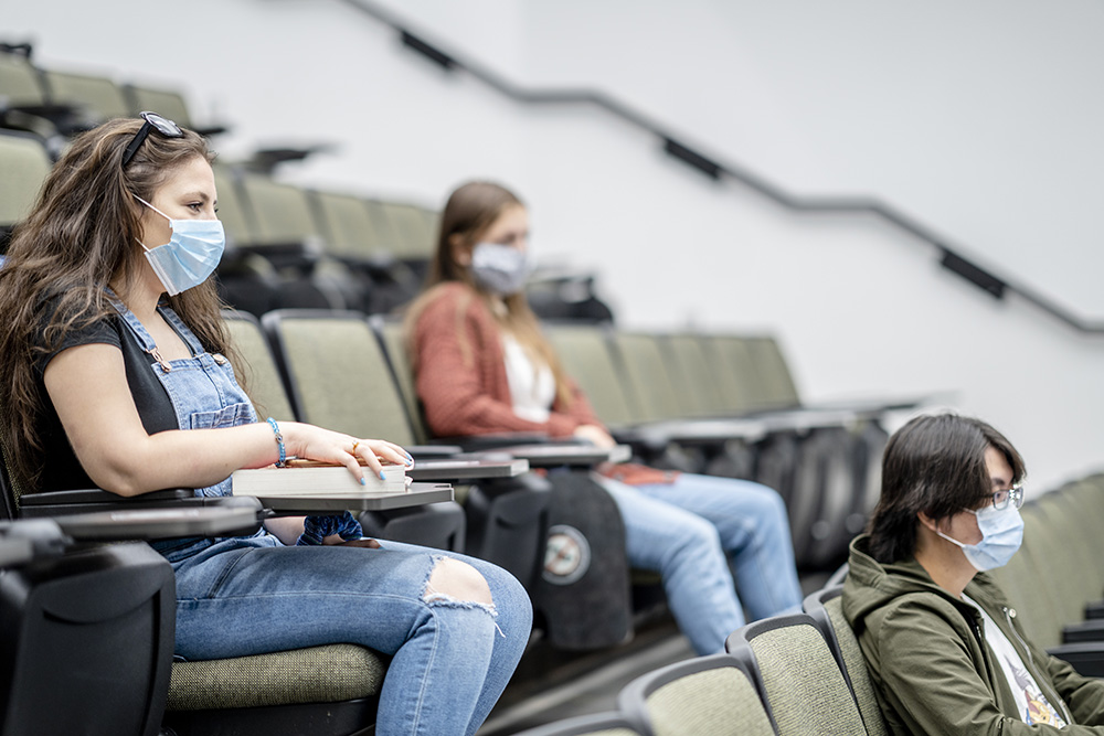 Students wearing protective face masks while sitting in a lecture hall
