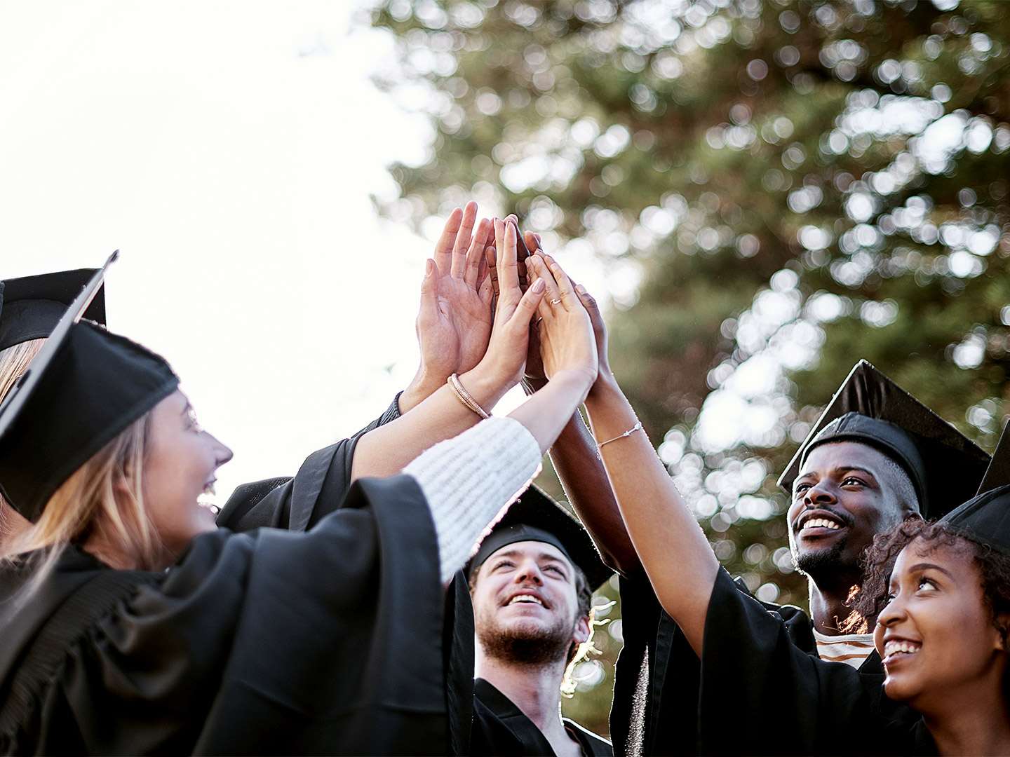 Group of smiling students in their graduation caps and gowns holding their hands together in the center