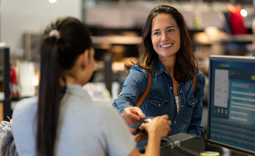 Cheerful female customer making a contactless payment with credit card at a furniture store smiling