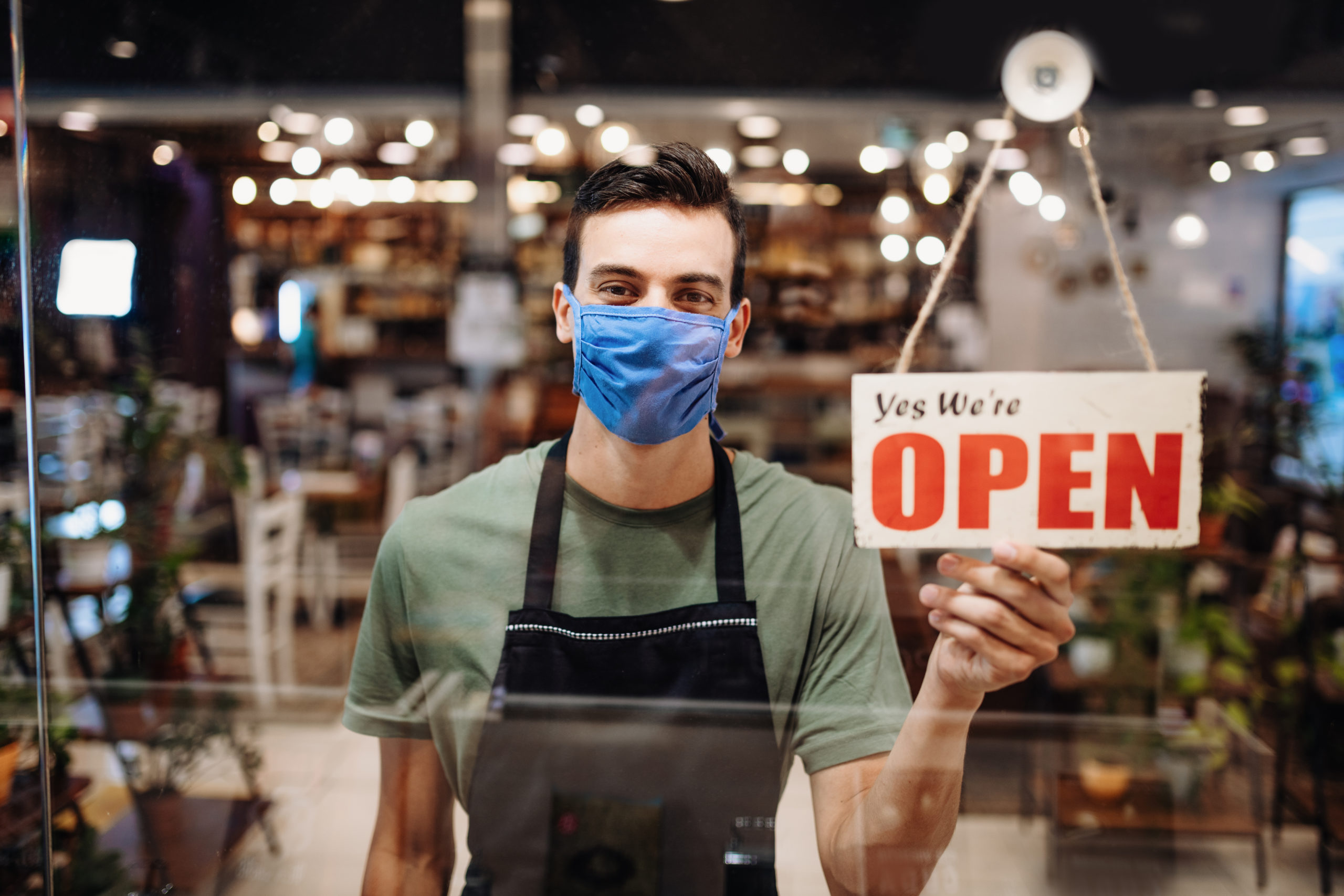 Cheerful young Latino waiter with face mask holding Open sign in cafe