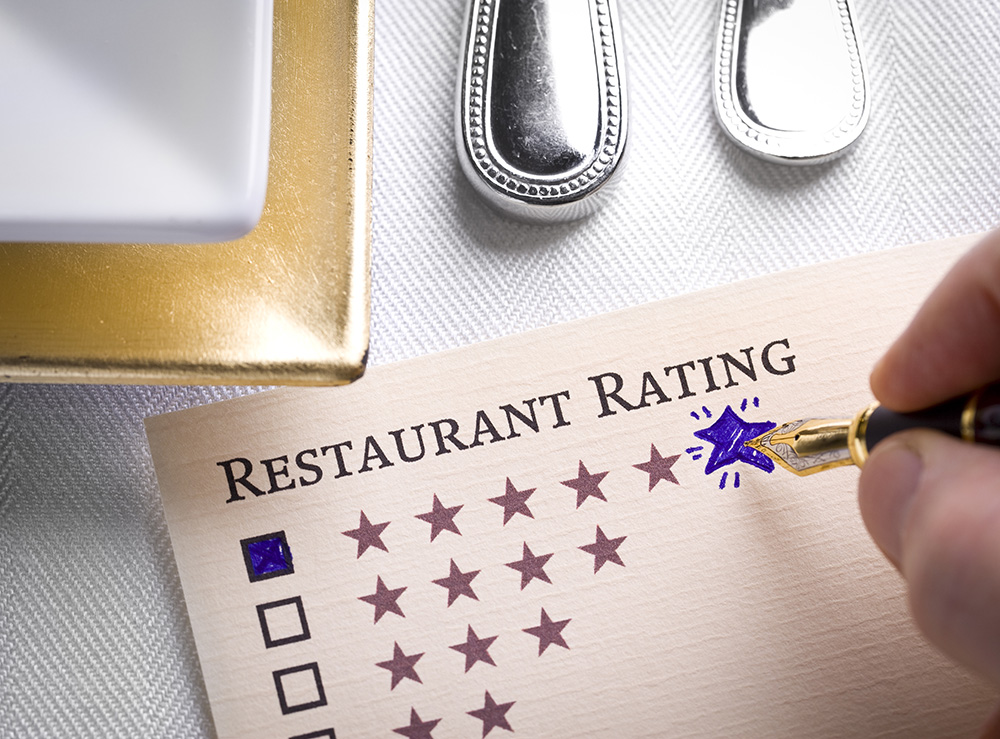 Restaurant Rating concept with pen and table setting.